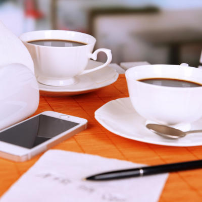 Two cups of coffee with pen and phone number on napkin on table with orange bamboo mat, on light background